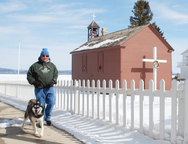 Petoskey resident Dennis Cassidy walks with a friend¿s dog, Daisy, past the waterfront St. Francis Solanus Indian Mission Church, Monday. The morning started out cold, with temperatures in the teens, but had warmed up to the high 30s by the afternoon, offering a hint of spring, but still a far cry from the temperature of one year ago, which, according to the National Weather Service, reached 80 degrees in Pellston on March 18, 2012. More snow is in the forecast for the next few days.
