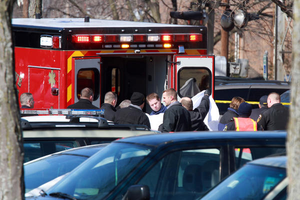 Emergency personnel remove the body of a pedestrian struck by a Metra train in Downers Grove.
