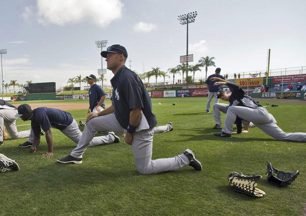 New York Yankees infielder Derek Jeter (C) stretches during a workout before a spring training game with the Philadelphia Phillies in Clearwater, Florida, March 19, 2013. REUTERS/Steve Nesius (UNITED STATES - Tags: SPORT BASEBALL)