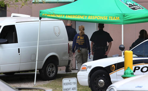 The medical examiner van is parked outside the dorm building as FBI evidence response team arrives Monday, March 18, 2013 to UCF after a student was found dead on campus. Explosives and guns were found in a dorm building,background, where she was evacuated from little after midnight.