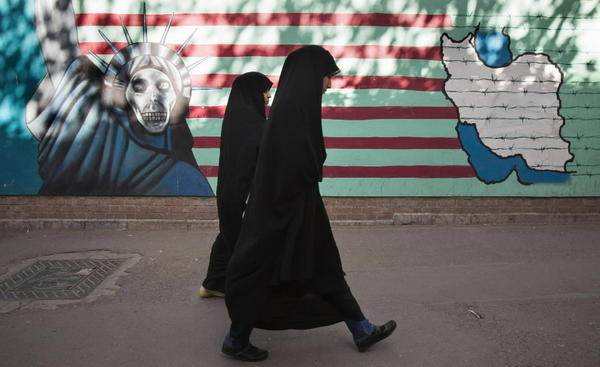 Iranian women walk past an anti-U.S. mural on the wall of the former U.S. embassy in Tehran.
