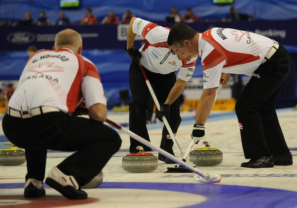 Team Canada moves the curling stone toward the target during the 2012 world championships in Basel, Switzerland.