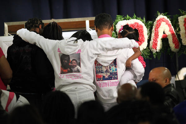 Mourners gather at the casket during the funeral for 6-month-old Jonylah Watkins.