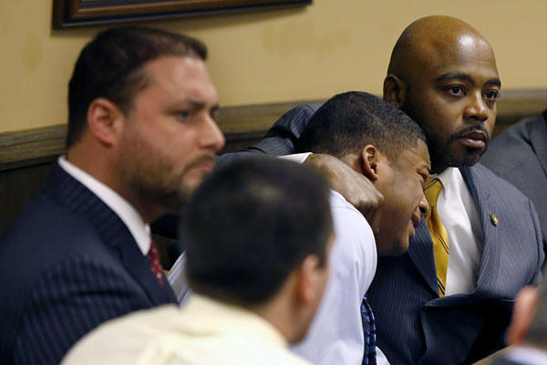 Defense attorney Walter Madison holds his client, 16-year-old Ma'Lik Richmond while Trent Mays, 17, sits in the foreground as Judge Thomas Lipps pronounces both defendants guilty of delinquent on rape and other charges.
