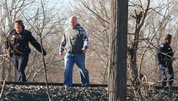 Chicago police walk along railroad tracks as they investigate a shooting that occurred near 58th Street and Princeton Avenue.