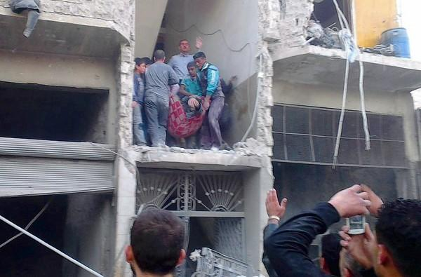 An injured man is carried from a building hit by an airstrike March 19 in Aleppo, Syria.