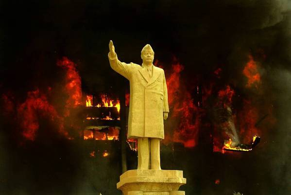 The Iraqi National Olympic Committee building, behind a statue of Saddam Hussein, goes up in flames in April 2003 as looters attack government structures in Baghdad.