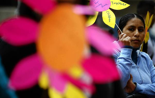 Manuela Lopez holds a flower-patterned protest sign during a rally to urge the Orange County Board of Supervisors not to cut funding to Latino Health Access, a nonprofit that helps the county's poorest residents.