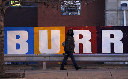 A pedestrian bundled up passes Jonathan Burr Elementary School on the first day of spring.