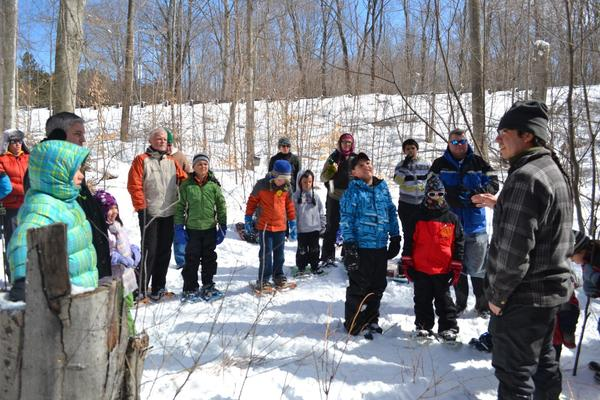 Doug Craven (far right), member of the Little Traverse Bay Bands of Odawa Indians, leads an expedition of about 50 people on a maple syrup-making workshop Sunday.