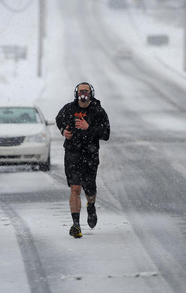 Travis Mainhardt of Wind Gap, doesn't let the snow bother him as he jogs down South Lehigh Ave. in Wind Gap for his daily exercise Tuesday afternoon.