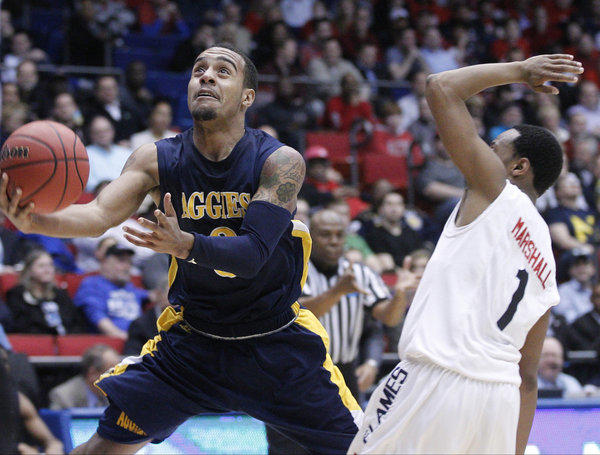 North Carolina A&T's Jeremy Underwood drives the lane against Liberty's Davon Marshall, right, in an NCAA tournament's game in Dayton, Ohio.