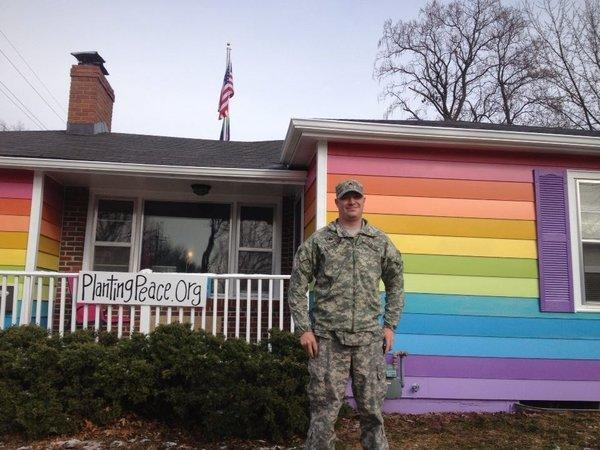 "An unidentified soldier poses in front of the ""Equality House"" across the street from the Westboro Baptist Church in Topeka, Kan."