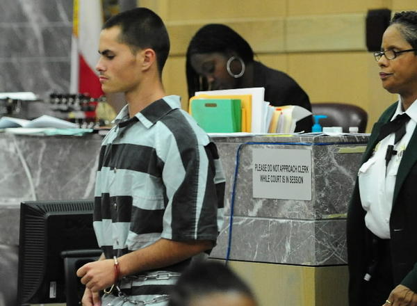 Denver Jarvis is led into a Broward courtroom on Wednesday, March 20, 2013. A judge reduced Jarvis' probation sentence for the burning of Michael Brewer from 21 years to 10.