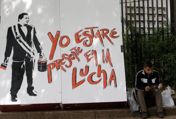 """At the annual book fair in Venezuela, a mural depicting former President Hugo Chavez reads, in Spanish: """"I'll be present in the fight."""""""