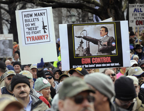 Protesters hold signs portraying New York Governor Andrew Cuomo as Adolf Hitler during a pro-gun rally at the State Capitol in Albany, New York.