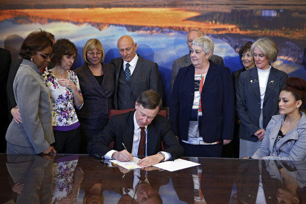Sponsors and family members of victims watch Wednesday as Colorado Gov. John Hickenlooper signs gun-control bills into law at the Capitol in Denver.