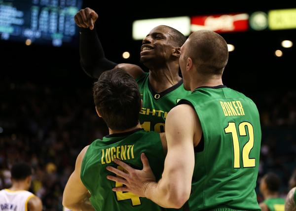 Oregon's Johnathan Loyd (10), Nicholas Lucenti (4) and Coleton Baker (12) celebrate the Ducks' win over UCLA in the Pac-12 championship game Saturday in Las Vegas.