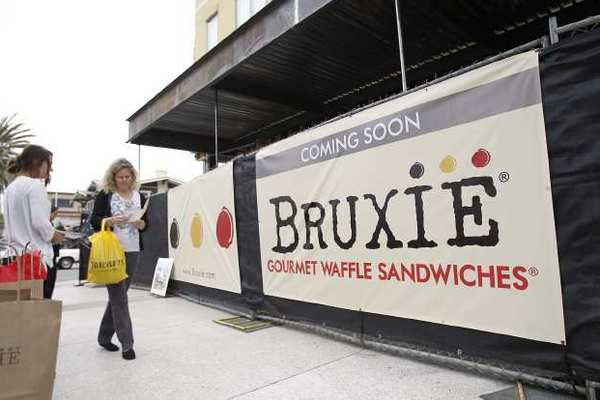 A woman inquires about Bruxie's latest store in Huntington Beach on Tuesday.