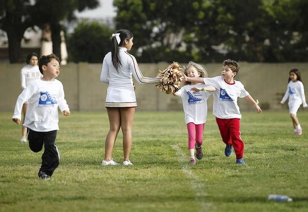 Angie Arroyo, 15, an Estancia High School cheerleader, high fives Isabella Zuniga, 6, and Gianluca Falcone, 6, during California Elementary School's jog-a-thon fundraiser on Wednesday.