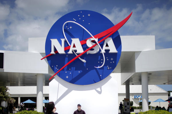 Tourists take pictures of a NASA sign at the Kennedy Space Center visitors complex in Cape Canaveral, Fla.
