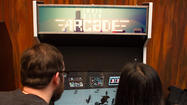"Rob Lach lovingly pats a hulking, pale-blue arcade cabinet with the Chicago flag painted on the side and a marquee that reads ""Indie City Arcade."""