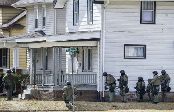 Officers surround a house in Fort Wayne, Ind., where police said a man suspected of killing a bus passenger earlier in the day was holding a 3-year-old child hostage.