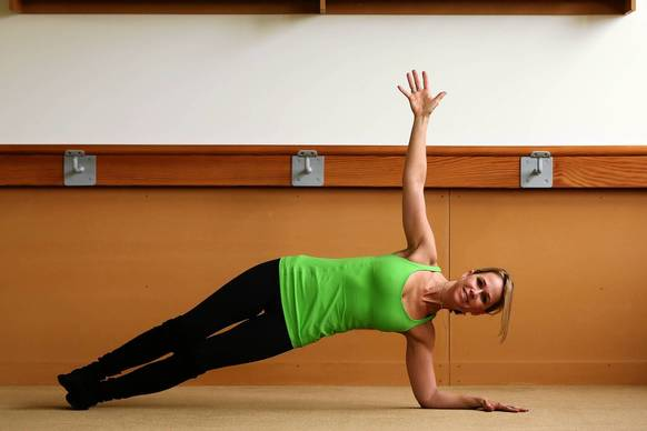 Begin in a traditional forearm plank with elbows under shoulders and forearms parallel. Make sure abdominals are pulled in and engaged before transitioning to the side.<br /><br />Slide palms toward your centerline so thumbs and forefingers connect. Then turn and stack your left hip on your right, and place your left palm on your left hip.<br /><br />Use abdominals to pull navel to your spine as you hug shins and thighs together. If you aren't completely stable, you can slide your top foot in front of you for a wider foundation.<br /><br />Reach left arm to sky, opening chest while pulsing left hip up 10 times.<br /><br />Slowly and with control move back to forearm plank. Repeat on the right side.