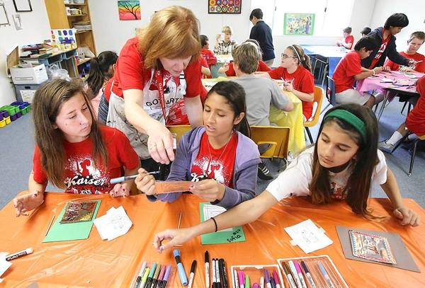 Sixth-graders Audrey Torrey, Sophia Velazquez and Greenley Weygand, left to right, listen as art teacher Caran Fahy helps them with a technique called metal tooling at Kaiser Elementary School on Wednesday.
