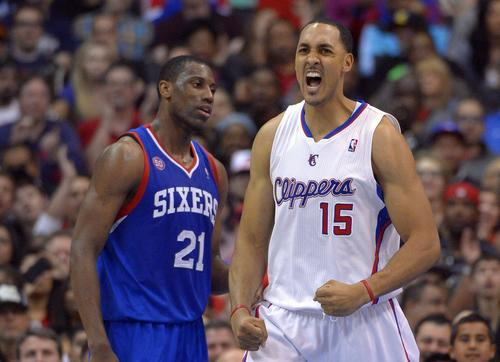 Clippers center Ryan Hollins celebrates after scoring against forward Thaddeus Young and the 76ers in the second half Wednesday night at Staples Center.