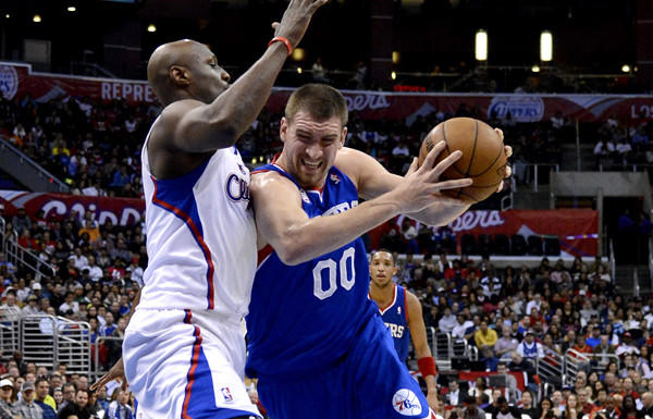 Clippers reserve big man Lamar Odom tries to cut off a drive by 76ers center Spencer Hawes in the first half Wednesday night at Staples Center.