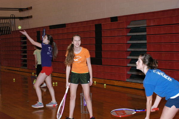 Jill Atwood (from left), Deana Graham and Adriana Dixon, all ninth-grade students at East Jordan High School, practice their serves indoors Wednesday because snow remains and continues to accumulate on the courts where their tennis team will practice this spring at Boyne Mountain.