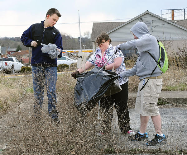 Members of the George Rogers Clark High School Beta Club volunteered their time after school Wednesday to remove litter along Boone Avenue and Vaught Road. Marena Stone battled the strong winds trying to hold open a trash bag for Addison Bradley, left, and Ashton Stamper to put litter in, right photo. Also helping with the cleanup was Ashton Wasson, Megan Wasson, and Beta Club sponsor Connie Cobb. This week is being observed as Commonwealth Cleanup Week. Litter along Colby and Iron Works roads is also being removed with help from the state Highway Department, Clark County Detention Center inmates, volunteers, and Clark County Solid Waste Coordinator Gary Epperson and his staff.