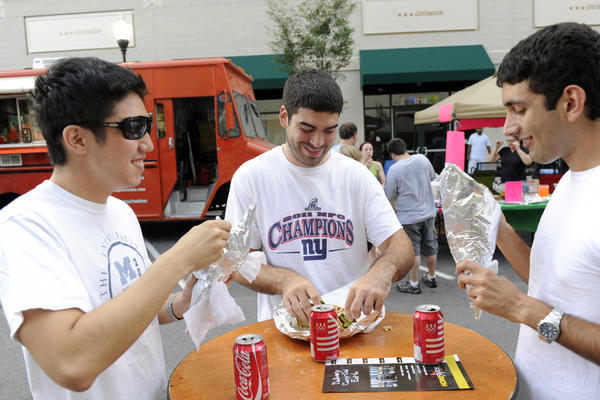Seung Cho, Matthew Finch and Adam Ardakanian enjoy entrees at the food truck rally at McHenry Row in July 2012.
