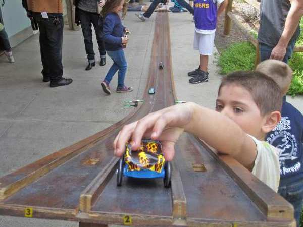 Luke Scherrer gets set to release his car on the practice track at the annual Pinewood Derby Race on a recent Saturday at the YMCA.