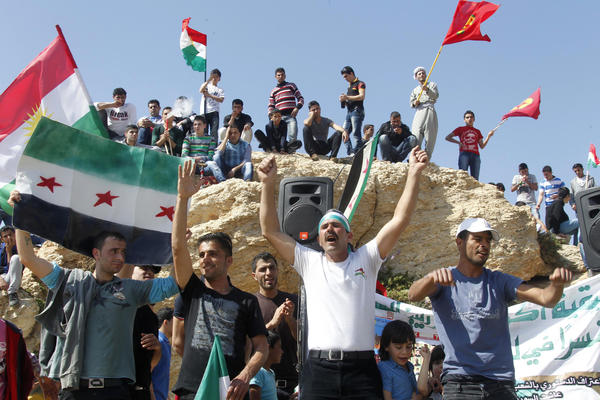 Demonstrators chant slogans as they hold Syria's opposition flags and Kurdish flags.