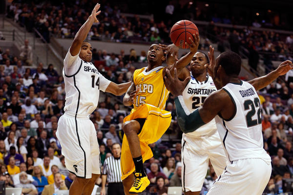 Erik Buggs of Valparaiso drives against Gary Harris (14), Derrick Nix (25) and Branden Dawson (22) of the Michigan State Spartans.