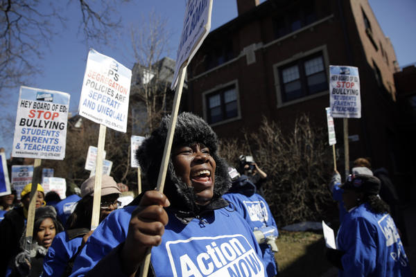 "Daphne Coleman, of Chicago, joins Action Now members protesting school closings in front of Chicago Board of Education member David Vitale's house in the 4900 block of South Woodlawn Avenue in Chicago during their ""School Board Bullies Bus Tour."""