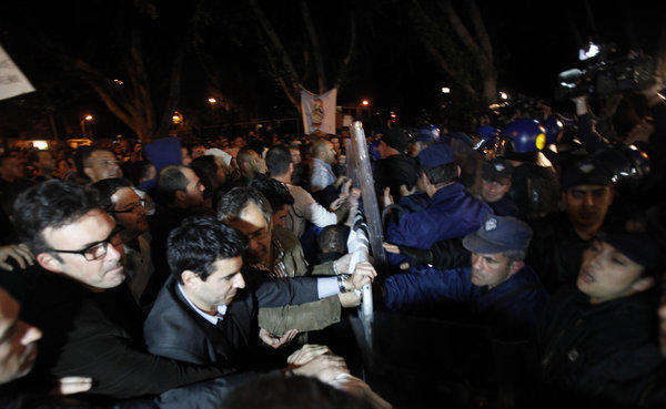 Demonstrators push barriers as riot police try to stop them during a protest outside the Cypriot parliament in Nicosia, Cyprus, Thursday, March 21, 2013.
