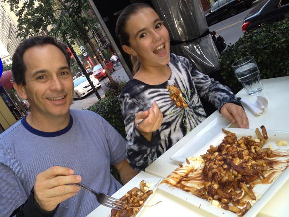 E.J. and Chloe Laviolette try poutine, a Quebec dish of French fries, gravy and cheese curds.