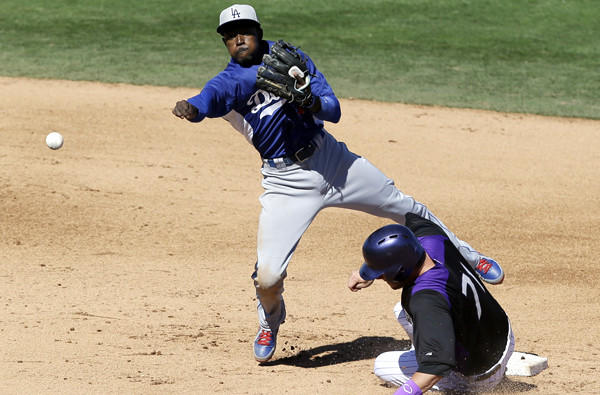 Dodgers shortstop Dee Gordon avoids Colorado's Kyle Parker on a throw to first base to complete a double play during an exhibition game earlier this month.