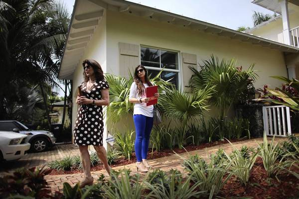 Valaree Byrne (left), of EWM Realtors International, shows a Miami home for sale last month to prospective home buyer Lauren Fili.