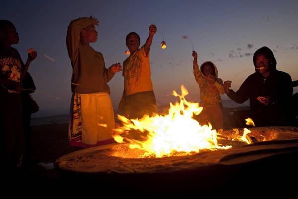 Members of the Sasser-Williams family of Los Angeles roast marshmallows at a fire pit at Dockweiler State Beach. Citing health concerns, air quality officials have proposed a year-round ban on open burning on all L.A. and Orange County beaches.