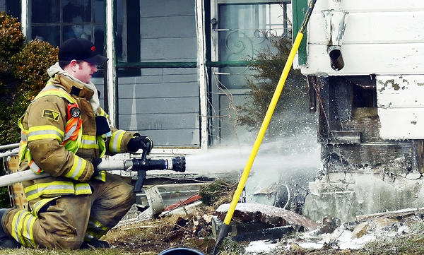 Firefighter douses an area where an electrical fire started at a house on St. Paul Road near Broadfording Road Thursday afternoon.