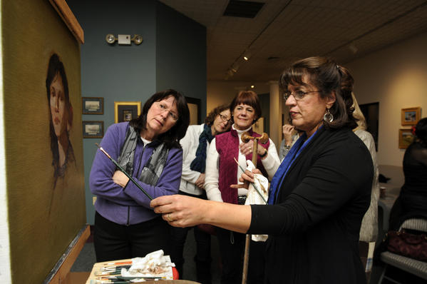 Artist Ellie Boyd, of Southbury, (left) leans in to watch as artist Sandra Wakeen demonstrates her technique while painting a model during a dueling demo with her identical twin sister and sculptor Susan Wakeen (off camera) at the Hartford Fine Art and Framing Gallery in East Hartford Thursday evening.  The sisters sculpted and painted a model and talked about their techniques as they worked to the group gathered for the demonstration.