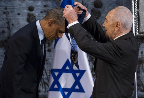 Israeli President Shimon Peres (R) presents US President Barack Obama with the Presidential Medal of Distinction, the highest civilian honor in Israel, during an official State Dinner at the President's residence in Jerusalem, March 21, 2013, on the second day of Obama's 3-day trip to Israel and the Palestinian territories.