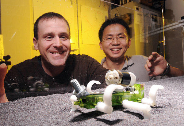 Georgia Tech professor Daniel Goldman and postdoctoral fellow Chen Li watch a robot traverse a track bed of poppy seeds as they study how animals and robots move on slippery granular surfaces.