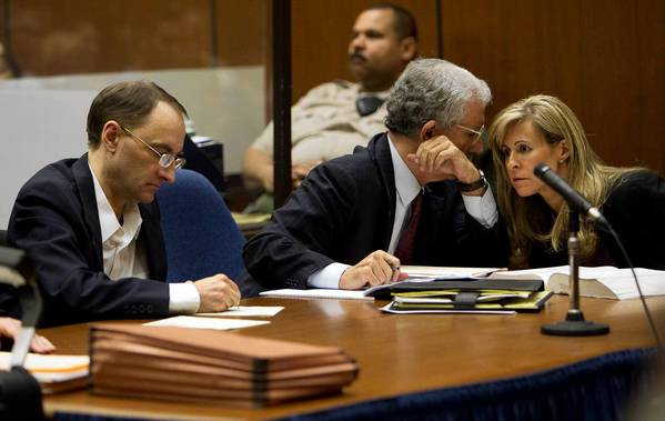 Christian K. Gerhartsreiter, left, jots down notes while two of his attorneys confer during opening statements of his murder trial. He is accused of killing John Sohus, who vanished with his wife in the spring of 1985.