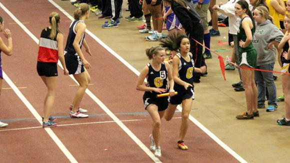 Lylan Dao hands off to Alanna Johnston in the girls¿ mile relay Wednesday at Saginaw Valley State University.
