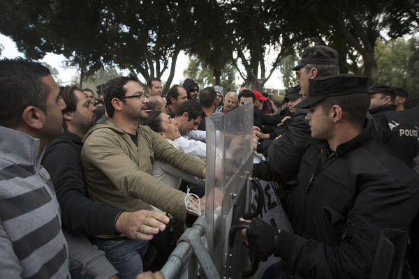 Police confront demonstrators attempting to pull down security barriers during a protest Friday outside the Cypriot parliament in Nicosia, Cyprus.